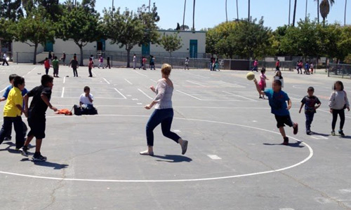 Jill Aldrich from the University of Rochester helps start and stabilize a friendly game of dodgeball on a public school playground in L.A.
